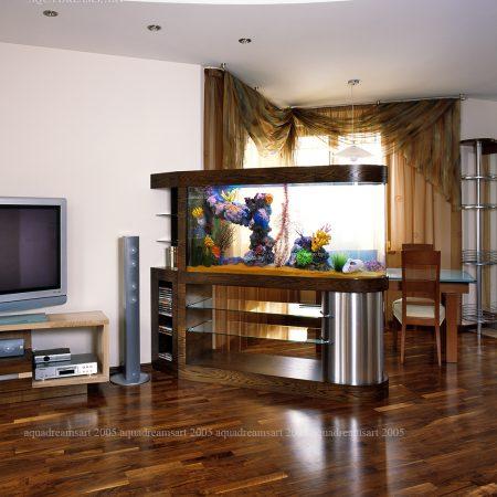 Этот аквариум стал отличным решением для зонирования пространства гостиной и столовой. Его мебельная отделка изготовлена из МДФ, фанерованного натуральным ореховым шпоном. Все аквариумное оборудование компактно размещено в цилиндре из матированной нержавеющей стали